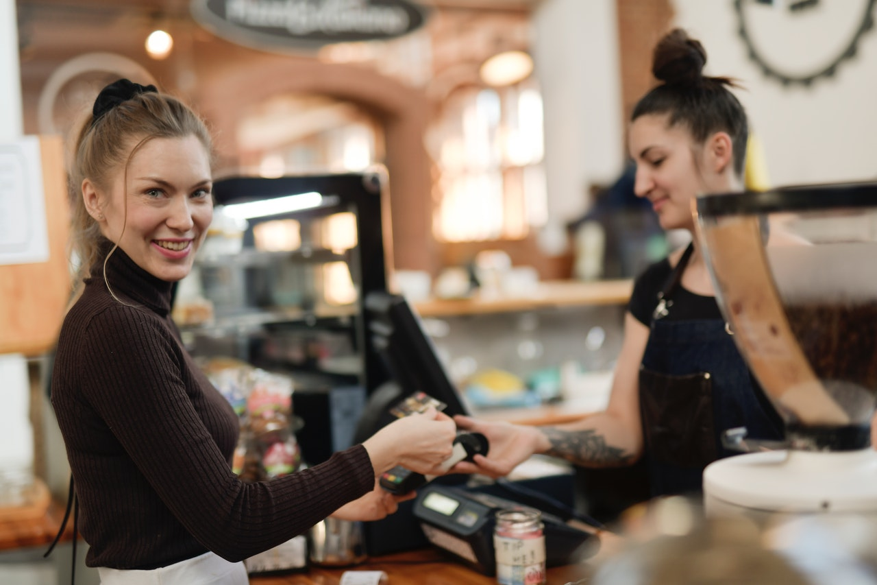 woman-in-black-long-sleeve-shirt-paying-at-a-cashier